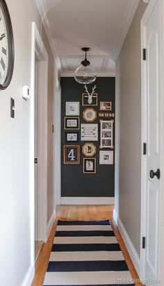 Make a gallery wall on a small surface with frames that contrast against the background color, like these mismatched shades of gold agains the dark blue-grey.