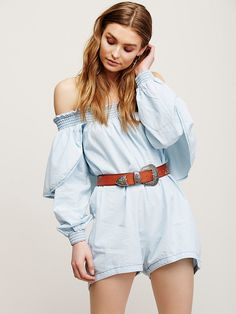 Texas Sugar Jumpsuit | Chambray off-the-shoulder romper featuring a smocked elastic band at the neckline and pleat detailing. Statement overlay in back with hip pockets.