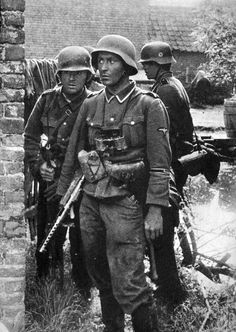 German Soldiers during World War II They look like SS but their collar insignia has been removed or retouched. Note the MP35 Bergmann SMG of the leader.