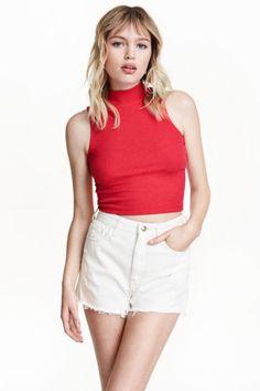 Camiseta corta de cuello alto: Camiseta corta en punto de canalé, sin mangas y con cuello alto.