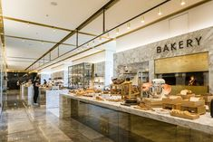 The Bakery The Bakery space is an energetic and active station celebrating the baking process through a showcase of kneading, mixing and baking. The bakery countertop is clad with gold Italian marble with brass inlay details and a bronze mirrored front facade.