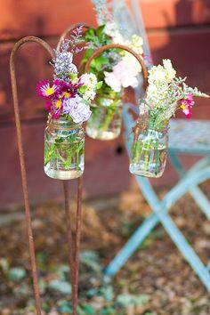 mason jar flower arrangements on shepherd's hooks.