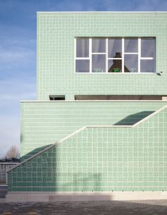 Glazed mint-green bricks alternate to create a basketweave pattern across the walls of this school building by Areal Architecten