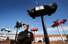 """Custom Car Art at G.I. Body Shop in Grand Island, Nebraska - photo by Barrett Stinson; Owner Fred Schritt enjoys doing body work and created six custom cars in 3 years, including 5 on poles: (from left) """"the Peppermint Kidd tow truck; a Model T driven by an old witch with the ogre Shrek in the rumble seat; a Karmann Ghia painted like the devil called Hell on Wheels; a Studebaker called the Mayberry Cruiser; and a 1960 Volkswagen sedan with a SpongeBob face and a body painted like the Red…"""