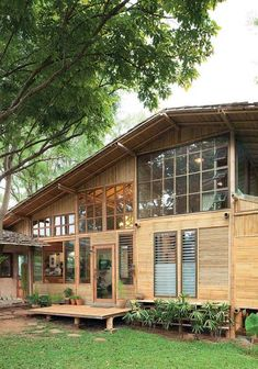 A bamboo house with modern appeal sits encompassed by its natural surroundings. It's also a medical clinic that says a lot about the doctor/homeowner's interest in the natural therapeutic concept. Discover the joy of a peaceful country setting. Modern Tropical House, Tropical House Design, Tropical Houses, Rest House, House In The Woods, Bamboo House Design, Bamboo Building, Thai House, Asian House