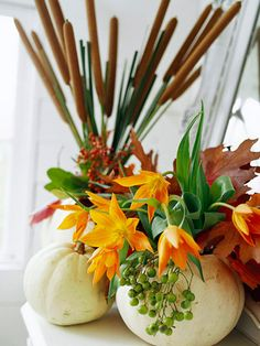 Lily Vase: White pumpkins make striking vases for fall flowers. Here, orange lilies and preserved fall leaves fill the front container, with cattails and berries behind in a second vase.