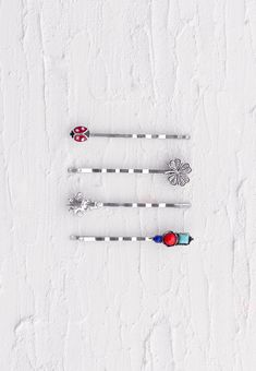 The Lucky Set in black nickel tones includes a lady bug,  four-leaf clover, star cluster, and an arrangement of colored stones such as red, blue, and turquoise. Set of 4 bobby pins.
