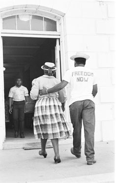 CORE worker accompanying a woman to the courthouse, where she will try to register to vote. | In 1964, 45% of Mississippi's population was Black, but less than 5% of Blacks were registered to vote state-wide. Registering voters in Batesville, Mississippi during Freedom Summer, 1964. (photo by Robert Brand)