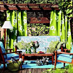 Create an outdoor room with fabric. This deck's setup is similar to an indoor living room arrangement. An all-weather rug anchors the furniture, and outdoor fabrics in pretty patterns cover the plush seat cushions. The arbor serves as a wall and ceiling, and panels hang from it like window treatments. Accents such as lamps and throw pillows complete the look.