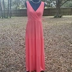 """New Coral Long Dress Cute sleeveless stretch long Charmin Coral dress by St Johns Bay has gathered V neck. Three tiered skirt measures 41"""" from back waistband. Top measures 12"""" from shoulder seam to waistband. Sleeve opening 18"""". Measures 17"""" across front bust from underarm to underarm and waistband measures 30"""". Rayon/spandex material. Cute and comfy. New with Tags St. John's Bay Dresses Maxi"""