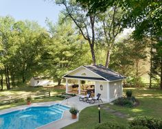 """This charming, transitional pool house features a unique open design that makes it half garden terrace, half indoor escape. Fretwork on the pool house's series of """"windows"""" adds a modern touch to the space while leaving it open for users to enjoy the bucolic, rural scene beyond."""