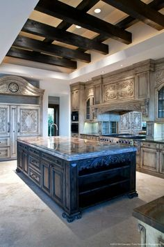 Twin chandeliers hang over one of two islands in this richly detailed kitchen. Natural hardwood floors, painted cabinet surrounds, marble countertops and patterned tile backsplash complete the look.