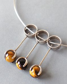 Necklace detail | Elis Kauppi for Kupittaan Kulta.  Sterling silver and tiger eye stone.  ca. 1970s