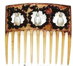 Rene Lalique: Horn, pearl, and diamond hair comb. Set with three baroque-shaped natural pearls and old-cut diamond surmounts, each suspended within a carved ivy mottled surround, to the horn comb, 1904-1906. This comb is being auctioned at Christies on 10 Nov. 2015. Sold for $47,437.
