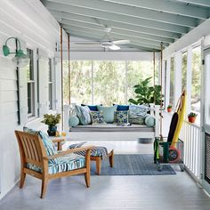 The shady front porch is designed as an easygoing extension of the indoor living areas, with a custom bed swing and a cushion and pillows. | Coastalliving.com