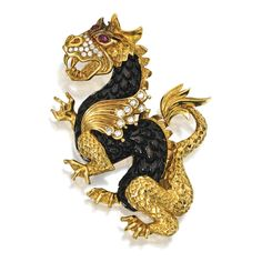18 KARAT GOLD, DIAMOND, RUBY AND WOOD BROOCH, VAN CLEEF & ARPELS. Designed as a dragon, the body composed of wood carved to resemble scales, the face and wings accented with round diamonds weighing approximately .50 carat, with two cabochon ruby eyes, signed VCA NY, numbered IKI02.26 and 35. With signed box.