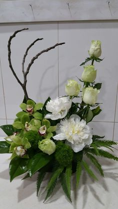 Modern arrangement of cymbidium orchids, roses and peony roses