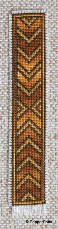 Stranded cotton on 14ct cream aida scrap using cross stitch. I began in the centre with the variegated mustard/brown cotton. Once done the contrasts that seemed to me to fit best were a lighter mustard yellow and very dark brown. I fringed the edges, more at the bottom. Backed with thin brown fabric fixed with Bondaweb.