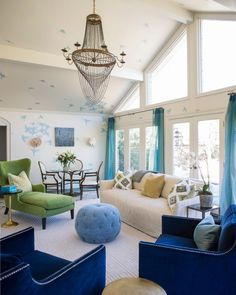 Whimsical design brings childlike wonder to a living room and makes kids (and guests!) feel right at home. Painted blue birds decorate the walls and ceiling in this bright white space. The pretty blue is carried throughout the room in the curtains and tufted pouf.