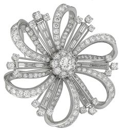 1930s Diamond Platinum Pin. The pin centers a sparkling GIA certified round cut diamond that weighs .73 carat. Graded as an I color with SI1 clarity, the stone is accentuated by dazzling baguette, and round cut diamonds weighing approximately 9.00 carat. c 1930