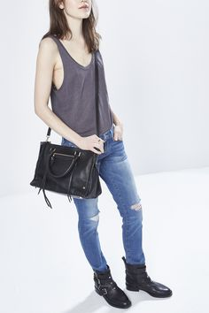 Meet this seasons musthave satchel featuring luxe details and seventies vibes. Simple studs  and a cool front zipper take this bag nextlevel while the spacious design stores your daily essentials with ease. This wellcrafted bag is complete with a stylish top handle and optional shoulder strap.