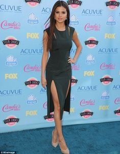 Going green: Selena Gokez showed off her extremely slender figure and slim legs in a stunning clinging dress with a double slit showing off her slender legs