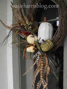 Pheasant Feather Floral Arrangement —check out the Susie Harris Blog if you're looking for fall decorating ideas like this simple grapevine wreath which is adorned with small gourds and pheasant feathers.