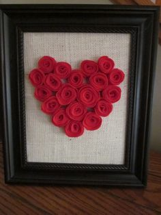 a bunch of small felt rosettes form the heart on top of burlap. love.