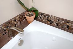 LOVE this...river rock and tile around tub