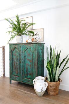 San Clemente Reveal | Part Two - Blackband Design  Jungalow style vignette in loft. Custom green antiqued dresser/cabinet.