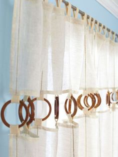 DIY updates to your old curtains. Cut 1/4 of the curtain length to leave at top, sew in loops and attach the wooden rings (hobby lobby, or napkin rings,etc), again sew in loops to bottom portion of curtains, and reattach! whalah!: