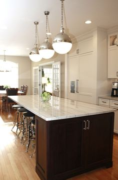 White Macaubas Quartzite countertops with white cabinets, a dark island, and light wood flooring. Kitchen by Stoneshop from Cherry Hill, NJ.