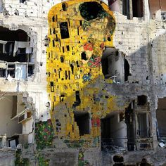 """Gustav Klimt's famous work """"The Kiss"""" (below) has been reproduced on a devastated building in Syria (top) by Syrian artist Tammam Azzam ... It is a kiss in the war zone...!"""