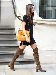 """""""We Are Your Friends"""" actress Emily Ratajkowski channeled the '70s in a black minidress with over-the-knee brown suede Saint Laurent boots during a London outing on Aug. 10, 2015."""