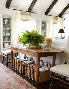 Layer antique elements like rustic woven baskets, a farm table, and rough hewn beams with clean-lined upholstery and white drapery.