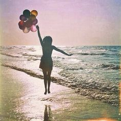 Silhouette of Girl holding bunch of balloons at the beach ...
