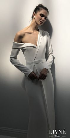 Livné White 2019 Wedding Dress - Eden Bridal Collection - JAMIE | Simple and unique bridal gown | Asymmetrical bridal wedding dress coat-look with a long sleeve on one side and cut out details at the shoulder of the other | #weddingdress #weddingdresses #bridalgown #bridal #bridalgowns #weddinggown #bridetobe #weddings #bride #weddinginspiration #weddingideas #bridalcollection #bridaldress #fashion #dress See more gorgeous bridal dresses by clicking on the photo