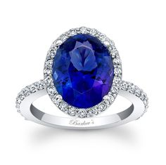 Tanzanite Ring - 7905LW - This tanzanite and diamond halo ring features an oval tanzanite center stone, encircled with shared prong set diamonds. The side shoulders of the dainty shank are embellished with diamonds to match for an added touch of elegance.  Also available in rose, yellow gold, 18k and Platinum.