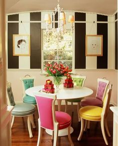 striped white and black walls, marble saarinen tulip dining table, turquoise blue, green, purple, yellow, pink, gray dining chairs and chandelier.