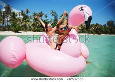 Summer lifestyle portrait of two pretty young girls friends swimming on air mattress in the ocean. Wearing bikini and mirrored sunglasses. Smiling and having fun. Positive emotions, bright colors