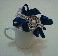 Tiara revestida em fita cetim azul marinho com casquetes em pérolas, strass e meia pérola decoradas com laços para encantar sua princesa. R$ 28,90