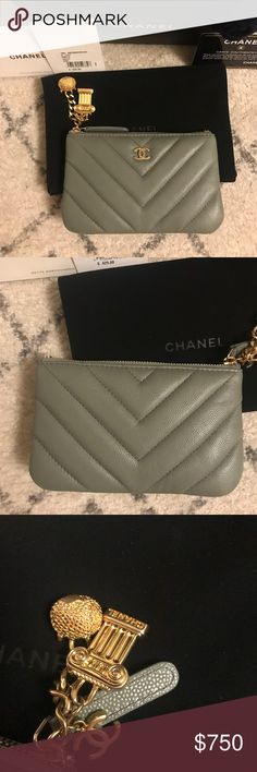 """Authentic Chanel Chevron O Case Charms Wallet Authentic limited edition. Purchased in January 2018. From the 2018 cruise collection. Comes with dustbag, box, authenticity card, care booklet, receipt and Camilla flower. Antique god hardware. Hardware charms looks faded but that is the look of the piece. Used a handful of times and in great condition. Measures 6"""" long by 4"""" high. Zip closure. No trades. CHANEL Bags Wallets"""