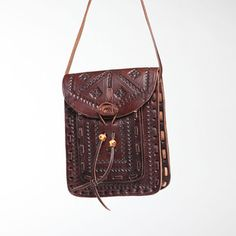 This charming Crossbody Leather Messenger Bag is hand-embossed and leather-stitched. With leather button and thong closure, under-flap pocket and adjustable strap, the bag is crafted of dark chestnut brown
