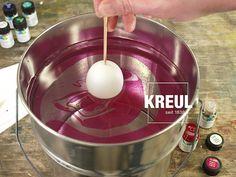 Step 3:  Marmorierfarbe gut schütteln und anschließend nahe der Wasseroberfläche aufträufeln. Dabei nicht mehr als 4 Farbtropfen pro Farbton und insgesamt nicht mehr als 15 Tropfen verwenden. Die Reihenfolge der aufgetropften Farbtöne beeinflusst das Marmoriermuster: Der erste Farbton wird vom zweiten verdrängt, so dass der zweite Farbton stärker zur Geltung kommt. Pastell-Farbtöne erhalten Sie, wenn pro Farbe nur 2-3 Tropfen verwendet werden.