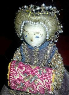 Pandora, fashion doll 1600.  Her face is in pale silk taffeta with eyes, eyebrows, nose and mouth embroidered with silk thread. The hair is real human hair in a darkish blond shade. The hairstyle is raised around the face, at the back it is pleated and pinned up decoratively. It is decorated with a row of pearls at the hairline and a diadem of gold tread and pearls at the hairstyle's highest point.