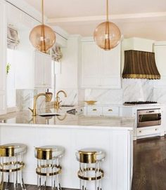 Laura Kirar for Arteriors Caviar Pendants in rose gold add the perfect touch of warmth to this glam kitchen as seen in Luxe Magazine.