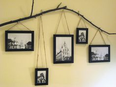 frames hanging by twine to a twig mounted on the wall =) LOVE!!