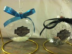 Harley Davidson ornament. Harley sign is a cupcake pick glued onto the front of a flat glass ornament. Glitter inside and bow hot glued on the front.