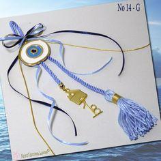 Χειροποίητο, ελληνικό γούρι για το 2018. Ένα μεταλλικό μάτι σε χρυσό χρώμα, με λευκό, γαλάζιο και μπλε σμάλτο, δεμένο σε μία γυαλιστερή σιέλ φούντα με σατέν κορδέλες. Στην άκρη κρέμεται ένα σπίτι με την ημερομηνία του '18 για να πάει καλά καινούριος χρόνος! Metal evil eye with white and light blue enamel decorated with satin ribbons a metal little house a '18 date and a tassel. Greek handmade gift for a happy new year.