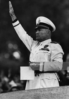 Benito Mussolini (1883 - 1945) taking the salute at a demonstration held by Italian firemen in Rome. The Duce distributed prizes and awards for valour.